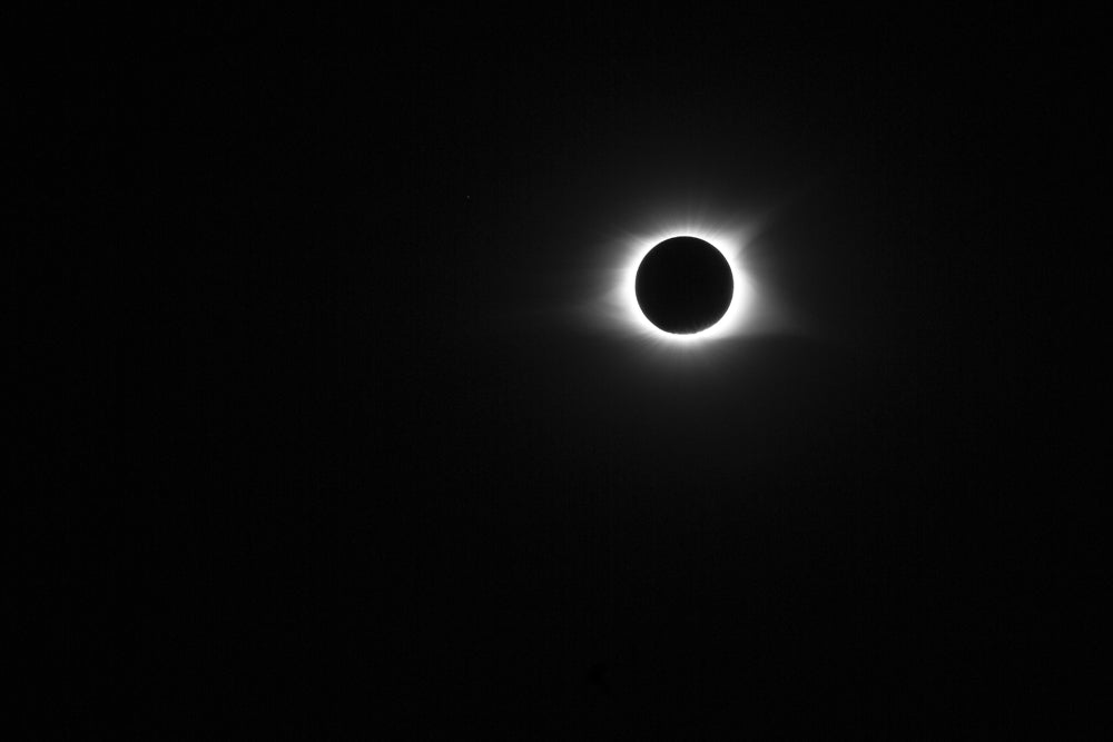 Black and white photograph of the sun in totality with its corona glowing around the moon during the great solar eclipse of 2017.