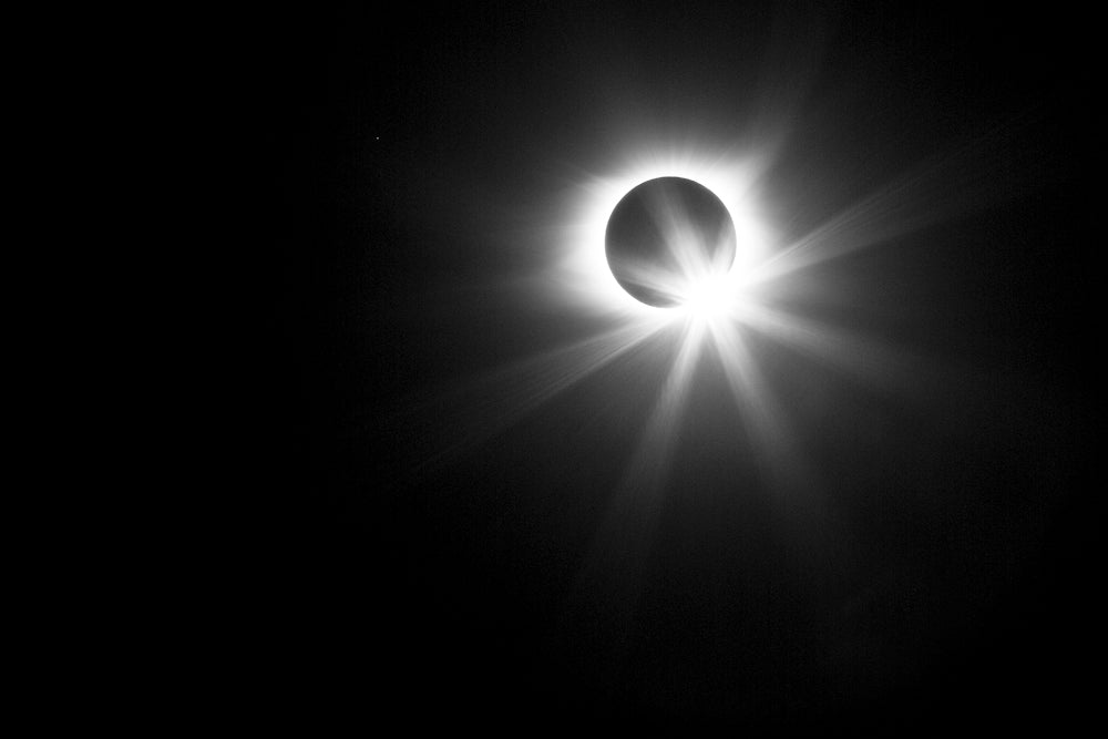 Black and white photograph of the sun just emerging with a burst of light from behind the moon in the great solar eclipse of 2017.