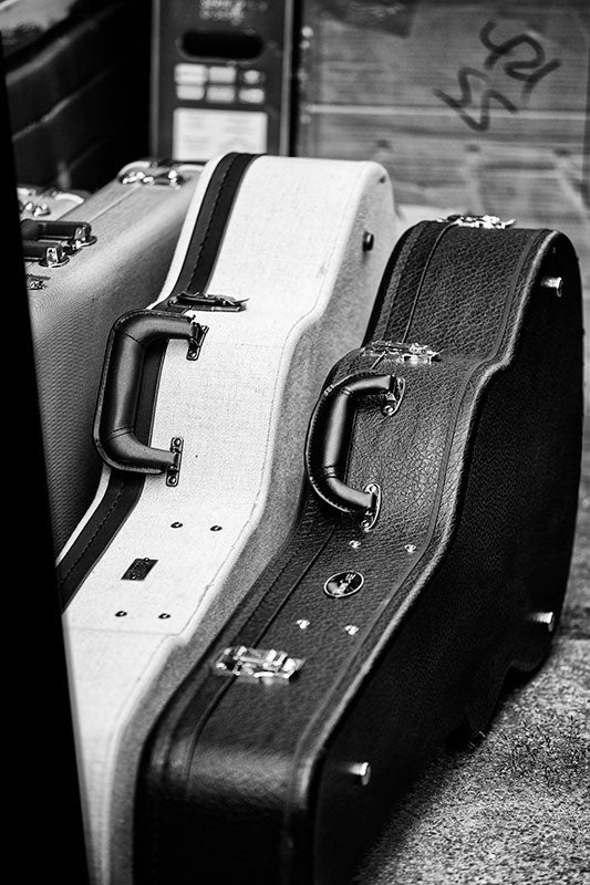 Black and white photograph of guitar cases and other gear waiting off stage at a gig in Nashville, Tennessee.