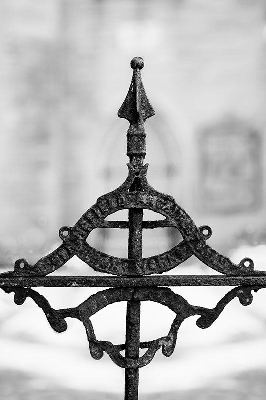 "Black and white photograph of a beautifully ornate but rusty detail on the antique iron gate at Holy Trinity Church, built circa 1852, near downtown Nashville, Tennessee. The church was designed by architects Frank Wills and Henry C. Dudley. The old gate detail is difficult to read, but it's a logo for the iron works that made the gate and fence, and says ""[Unknown] Architectural Iron Works."""