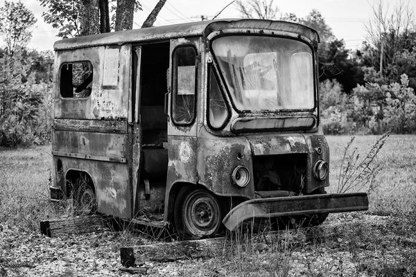 "Black and white landscape photograph focused on a small rusty and abandoned Postal Service truck parked in a field. On its side is an old triangular Civil Defense logo, which says in a circle around the CD icon, ""This is a unit of your Civil Defense."""
