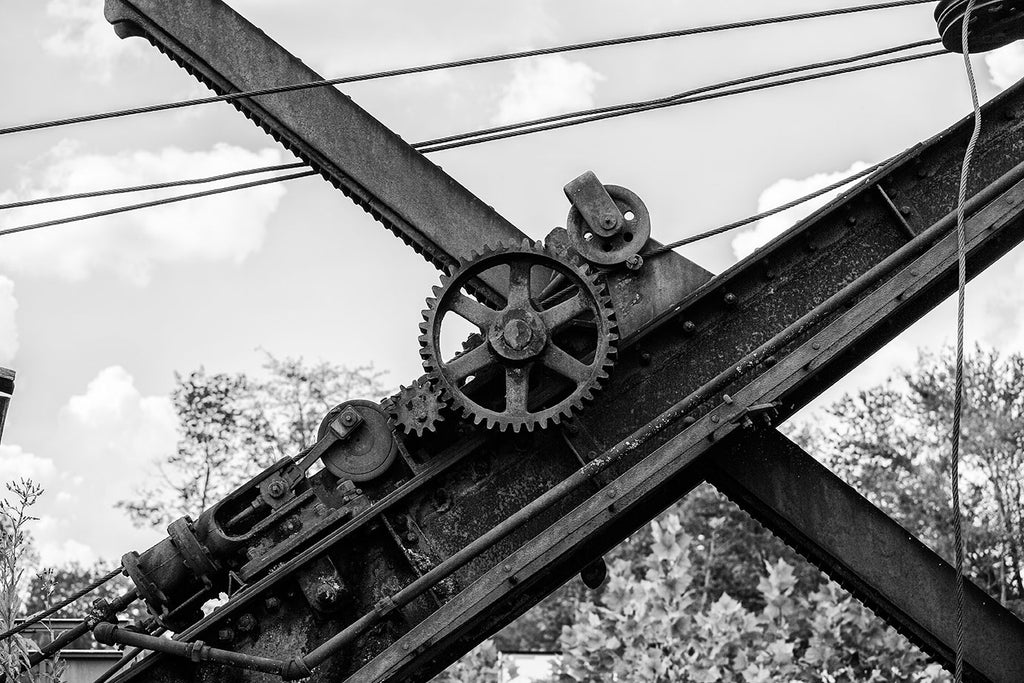 Black and white photograph of the gears and cables of a rusty, old steam shovel abandoned in a grassy rural pasture.