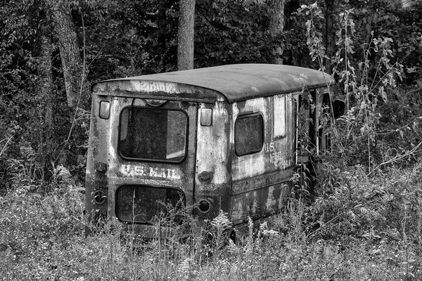 Black and white photograph of a rusty, old US Mail truck abandoned in a grassy field.