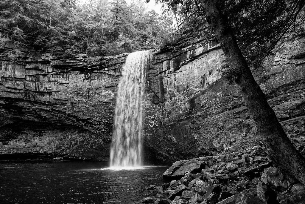 Black and white landscape photograph of a waterfall in soft light, emphasizing the whitewater of the river spilling over the edge of the cliff, and the high rocky walls of the basin that surrounds the pool at the base of the falls.