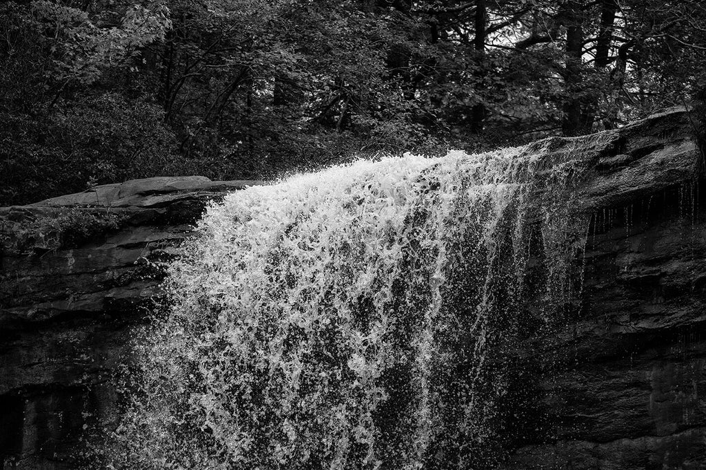 Black and white landscape photograph of the crest a waterfall in dramatic light, capturing individual water droplets in mid-air.