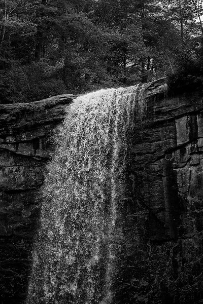 Black and white landscape photograph of a waterfall in dramatic low light, emphasizing the whitewater of the river spilling over the edge of the cliff. This photograph captures many of the individual water droplets in mid-air.