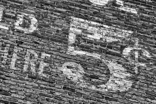 "Black and white photograph of a fading five-cents ""ghost sign,"" a historic advertisement that was painted on a brick wall many decades ago."