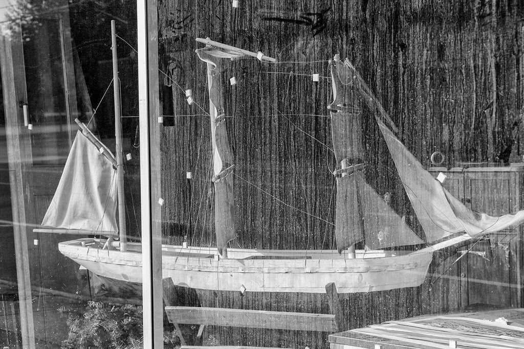 Black and white photograph of a model of a tall sailing ship displayed behind a dirty, streaked store window.