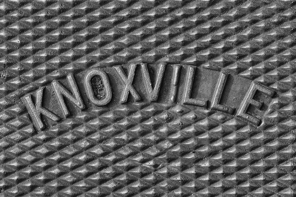 "Black and white photograph of the word ""Knoxville"" curved across an iron utility cover on a sidewalk in Knoxville, Tennessee."