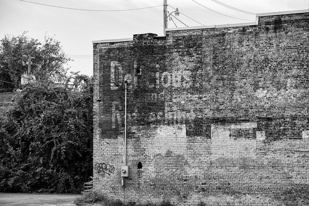 "Black and white photograph of a fading, peeling ghost sign ad on the side of an old brick building. The most prominent legible word is ""Delicious."""