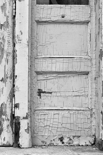 Black and white photograph of cracked and peeling paint on the door of an abandoned building.