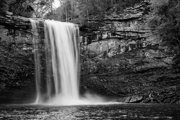 Black and white landscape photograph of a waterfall shot in long-exposure to capture the blur of the whitewater as it splashes into a basin below.