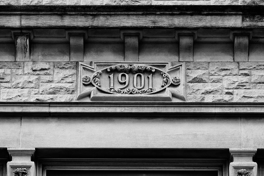 Black and white photograph detail of a decorative date placard that says 1901, on a historic Union Street building in Nashville, Tennessee. Builders of this era always dated their structures, as though they expected them to last into posterity. And, many of them have.