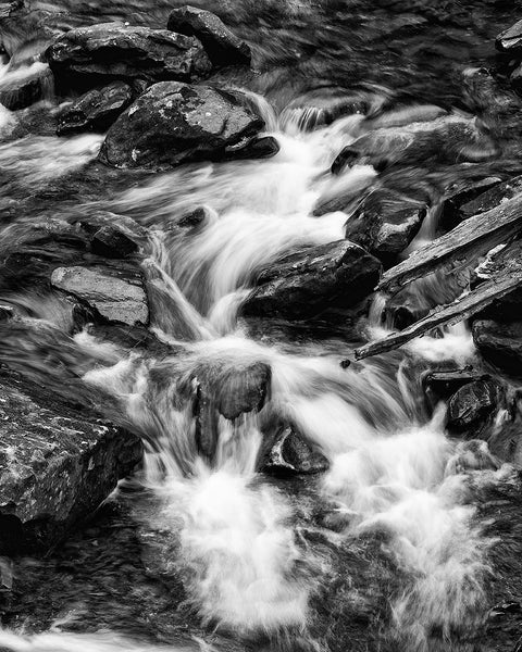 Dramatic black and white landscape photograph of whitewater rapids in a rocky canyon stream, with the water blurred by long-exposure.