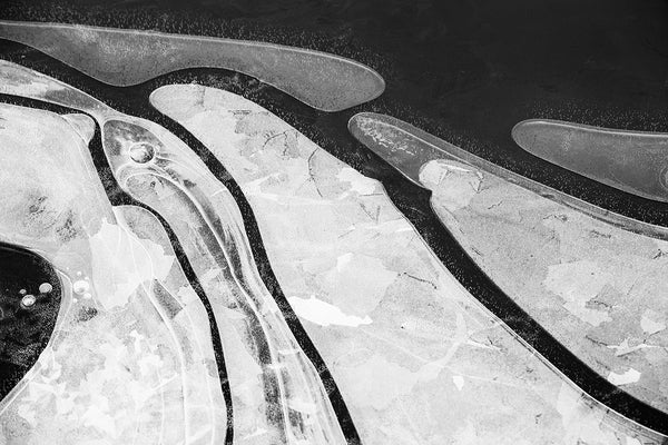 Black and white landscape photograph, abstract composition pond ice formed along the shoreline. A natural abstraction formed by organic shapes.