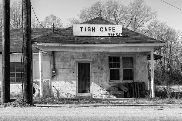 Black and white photograph of abandoned cafe with cartons and pallets stacked on the front porch in Tishomingo, Mississippi.