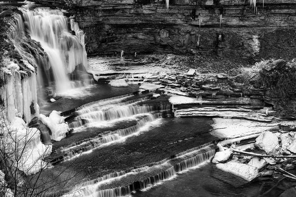 Black and white landscape photograph of icy winter waterfalls surrounded by snow and icicles seen from above.