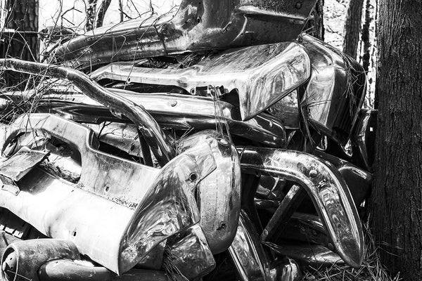 Black and white fine art photograph of big chrome bumpers from vintage American automobiles piled on top of each other in the woods.