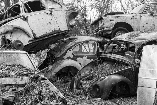 Black and white photograph of VW Beetles and other cars piled up in a discontinued junkyard.