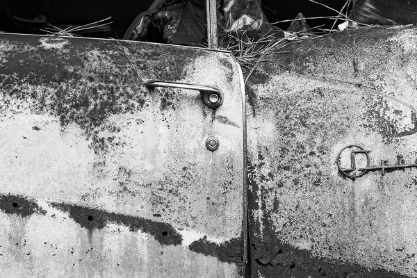 Black and white fine art detail photograph of the rusty driver's side door on a classic American car, junked and abandoned in the forest.