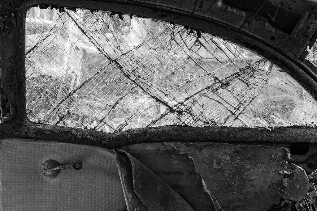 Black and white fine art photograph of the interior of an antique roadster, which has seen better days. The window is fractured in beautiful patterns, but the torn interior provides period context.