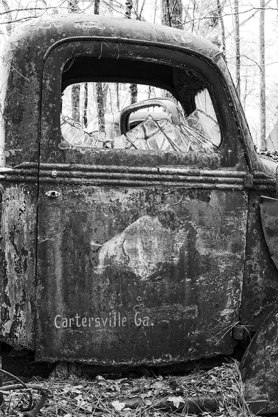 Black and white fine art photograph of a rusty, abandoned antique truck with a faded rhinoceros painted on it's heavily weathered door.