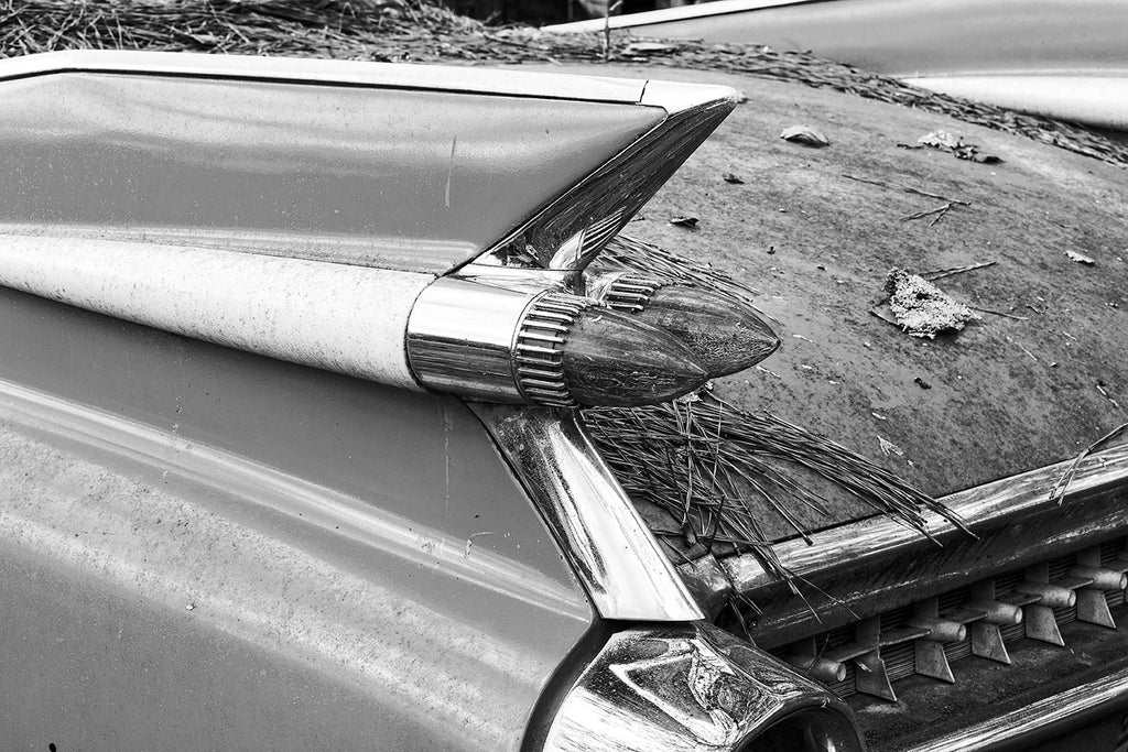 Black and white fine art photograph of a design detail — the rocket-style tail fin and tail lamps — on a rusting, abandoned classic American car.