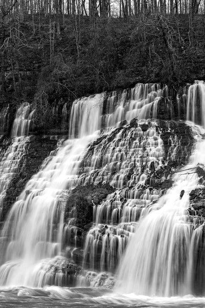 Black and white landscape photograph of a wide waterfall cascading in streams down an entire mountainside.