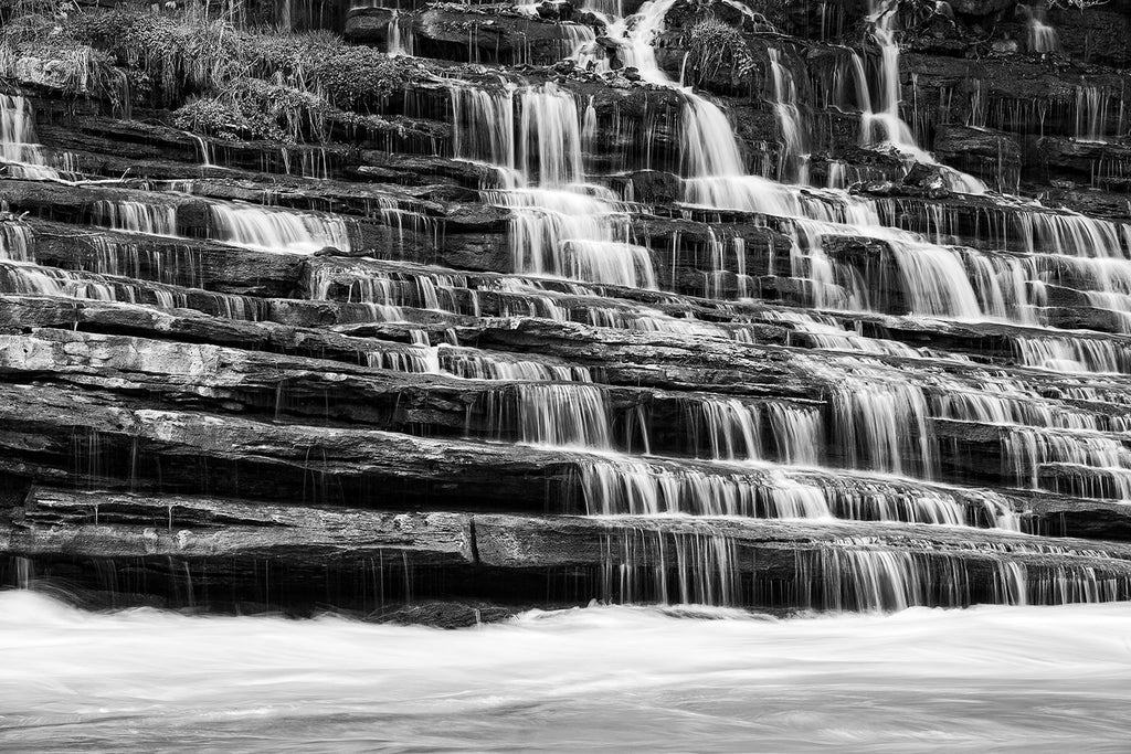 Black and white landscape photograph of a waterfall cascading down terraced rock ledges into a rushing river.