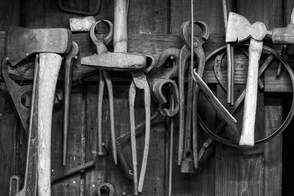 Black and white fine art photograph of a collection of rusty tools hanging on the wall of a working blacksmith shop.