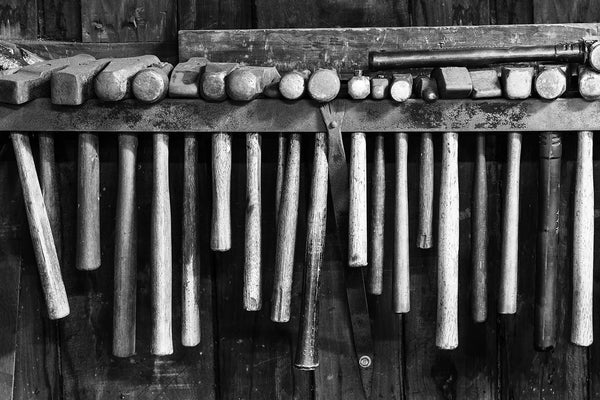 Black and white fine art photograph of a row of rusty hammers hanging on the wall of a working blacksmith shop.