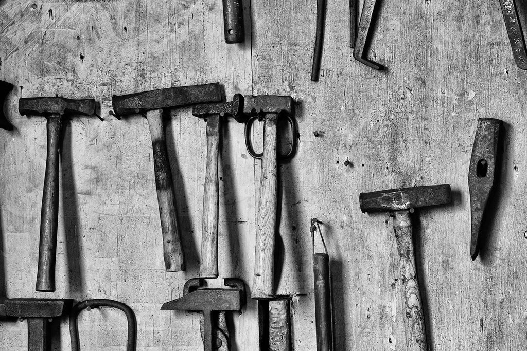 Black and white fine art photograph of tools hanging on the wall of a working blacksmith shop.