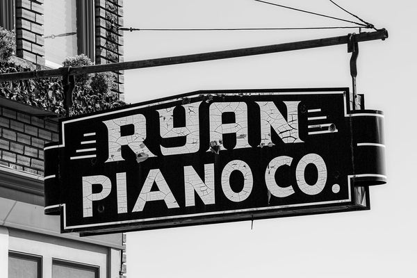Black and white photograph of the now closed Ryan Piano Co. in beautiful downtown Florence, Alabama. The sign has nice craquelure pattern in the paint of the letters. The business has been closed since at least 2001.