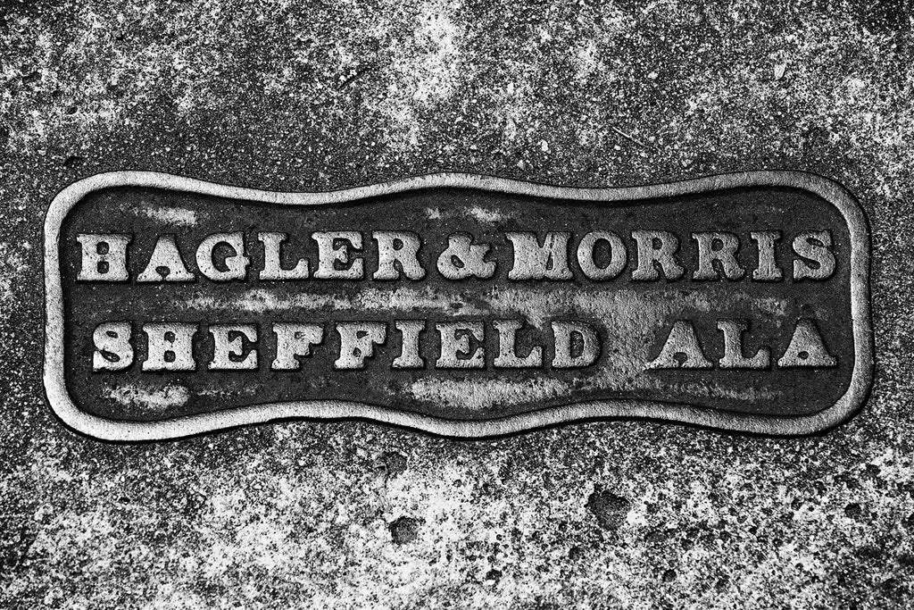 "Black and white photograph of an old sidewalk marker that reads ""Hagler & Morris Sheffield Ala."""