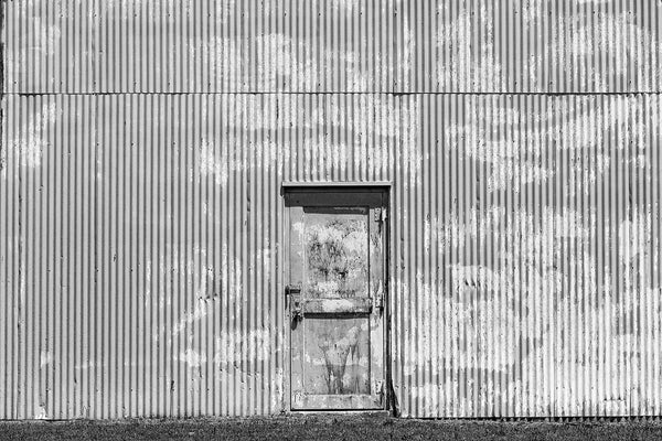 Black and white photograph of a tin industrial building with a grimy door set into a wall with strong vertical ridges.
