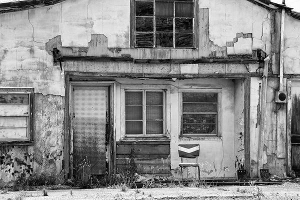 Black and white photograph of a shabby house with a vintage chair on the front porch.