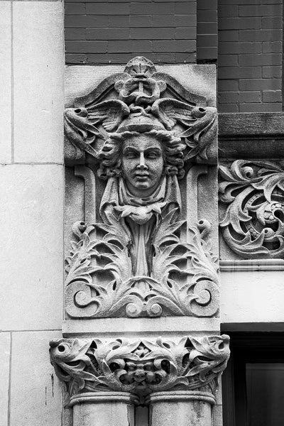 "Black and white photograph of a carved face on the Drhumor Building (pronounced ""drummer"") on 48 Patton Avenue in downtown Asheville, North Carolina. Built in 1895, the building features a set of carved faces, believed to have been modeled by local citizens, created by English sculptor Frederick Miles, who also worked on the nearby Biltmore Estate.  This photograph is one of a set of six, designed to be displayed together."