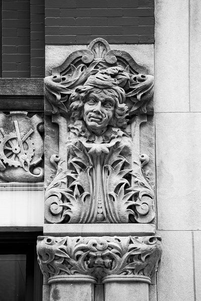 "Black and white photograph of a man's face carved on the Drhumor Building (pronounced ""drummer"") on 48 Patton Avenue in downtown Asheville, North Carolina. Built in 1895, the building features a set of carved faces, believed to have been modeled by local citizens, created by English sculptor Frederick Miles, who also worked on the nearby Biltmore Estate. This photograph is one of a set of six, designed to be displayed together."