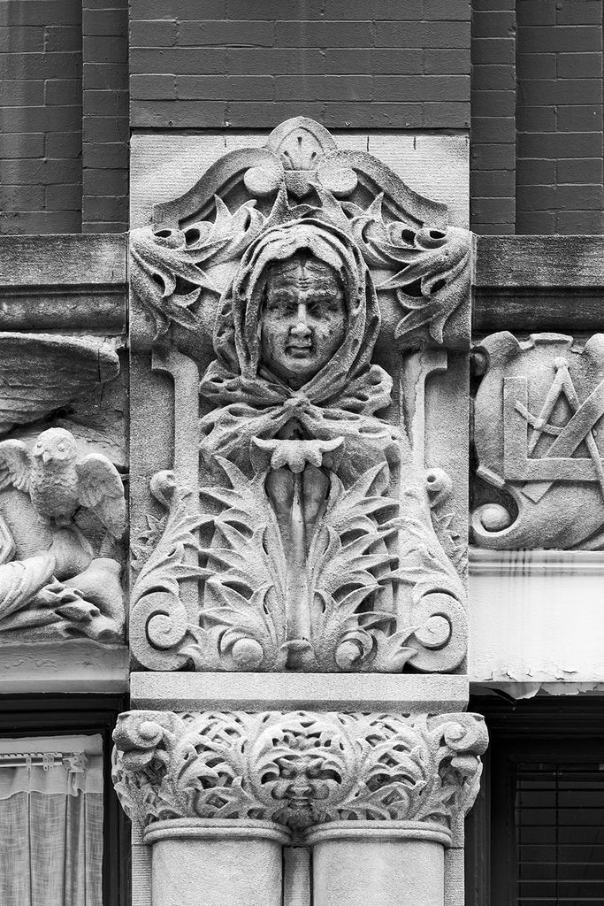 "Black and white photograph of a woman's face carved on the Drhumor Building (pronounced ""drummer"") on 48 Patton Avenue in downtown Asheville, North Carolina. Built in 1895, the building features a set of carved faces, believed to have been modeled by local citizens, created by English sculptor Frederick Miles, who also worked on the nearby Biltmore Estate.  This photograph is one of a set of six, designed to be displayed together."