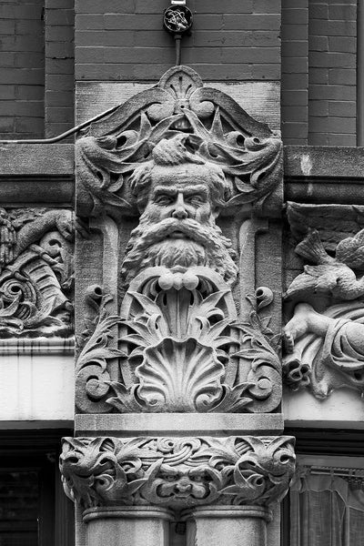 "Black and white photograph of a bearded man's face carved on the Drhumor Building (pronounced ""drummer"") on 48 Patton Avenue in downtown Asheville, North Carolina. Built in 1895, the building features a set of carved faces, believed to have been modeled by local citizens, created by English sculptor Frederick Miles, who also worked on the nearby Biltmore Estate.  This photograph is one of a set of six, designed to be displayed together."