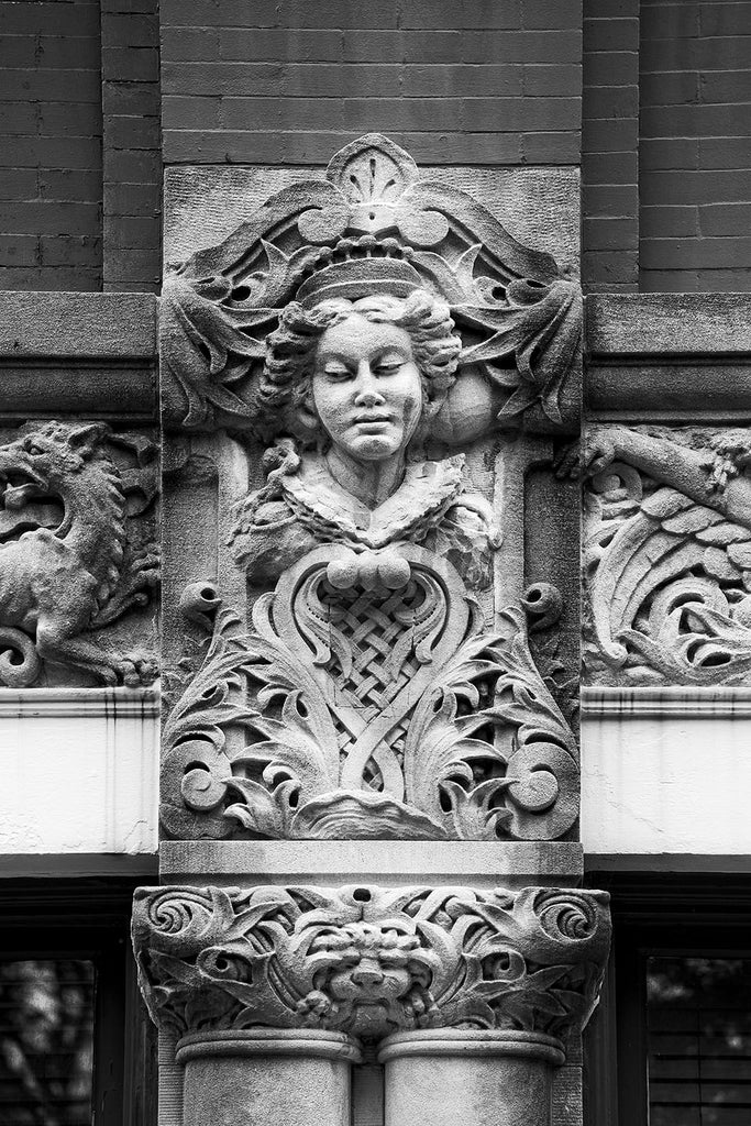 "Black and white photograph of a young woman's face carved on the Drhumor Building (pronounced ""drummer"") on 48 Patton Avenue in downtown Asheville, North Carolina. Built in 1895, the building features a set of carved faces, believed to have been modeled by local citizens, created by English sculptor Frederick Miles, who also worked on the nearby Biltmore Estate.  This photograph is one of a set of six, designed to be displayed together."