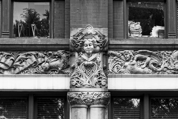 Black and white photograph of a fantastical carved frieze on the exterior of 48 Patton Avenue in downtown Asheville, North Carolina. The sweeping fantasy of the mythical creatures and iconic figures contrasts (and clashes) with the reality of the stacks of paperwork seen in the windows of the modern law office that inhabits the building.