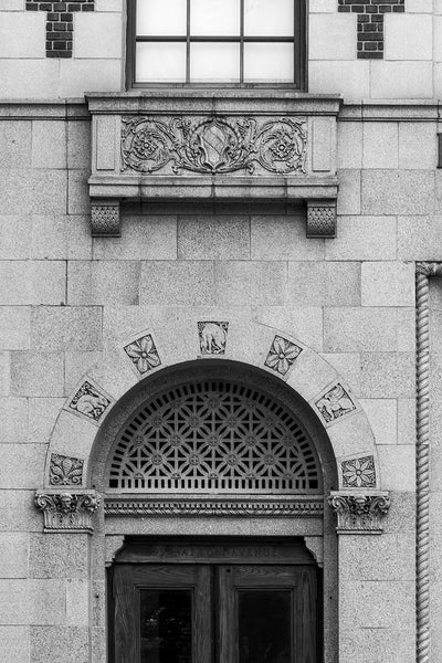 Black and white architectural detail photograph of the facade of 93 Patton Avenue in Asheville, North Carolina, featuring ornate decorative stone carvings.