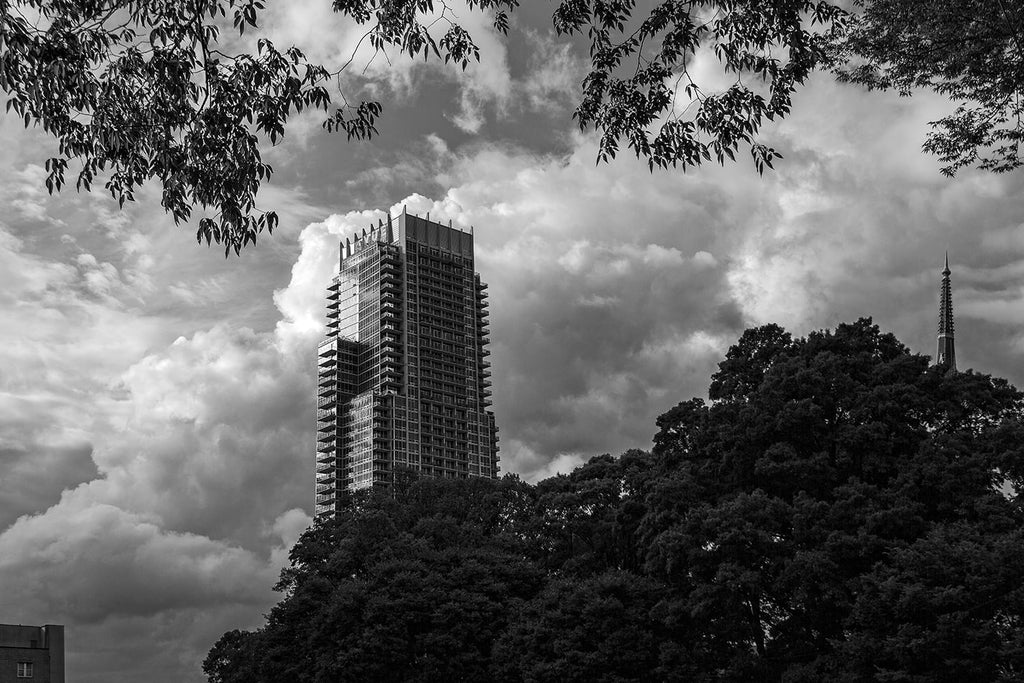 Black and white cloudscape photograph of Charlotte, North Carolina featuring The Vue, the fifth tallest building in Charlotte.