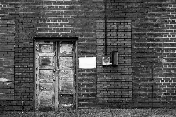 Black and white photograph of an abandoned building—the back side of an old storefront—in a small town in North Carolina. The cracked wooden doors, varying brick patterns, and repeated rectangle motif make this composition interesting.