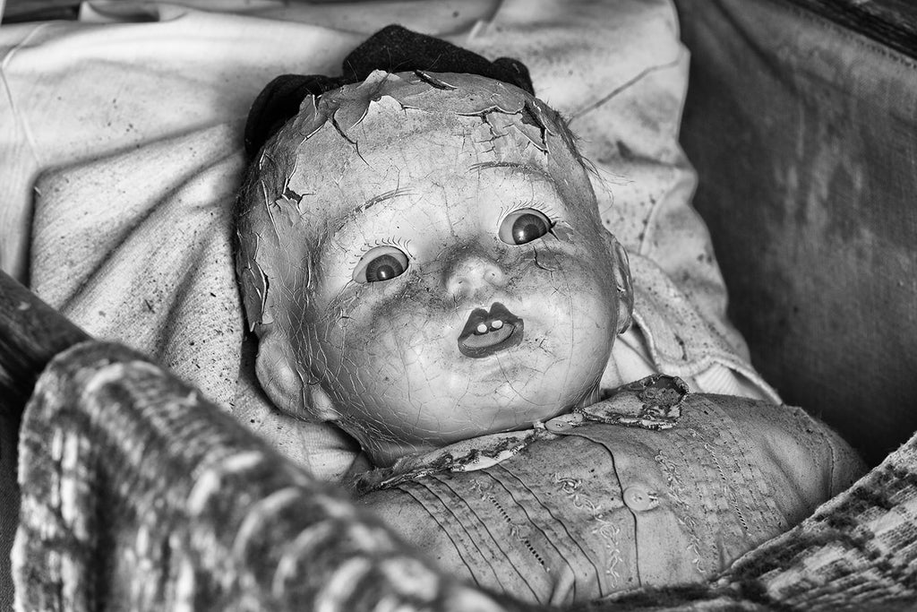 Black and white photograph of a beautifully cracked and dusty antique doll with a somewhat frightening look on its face.