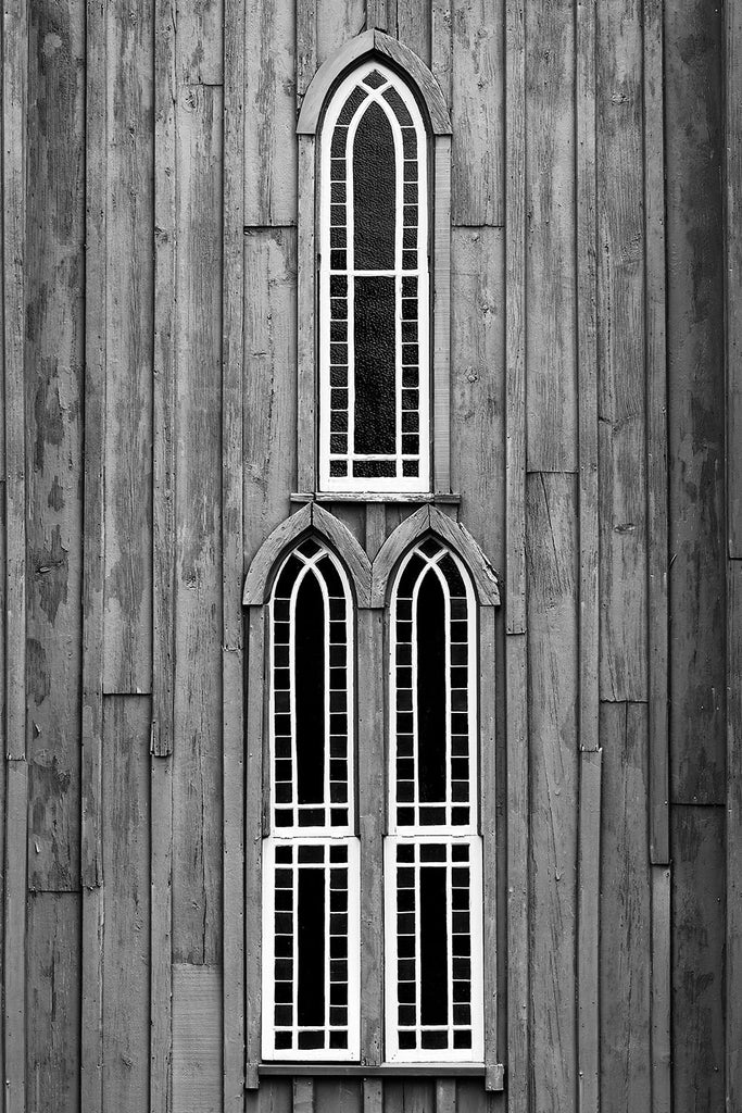 Black and white photograph of a trio of windows on a historic Gothic Revivalist church constructed from wood in the mid 1850s.
