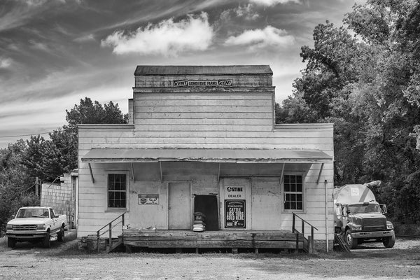 Black and white architectural photograph of an old, wooden agricultural feed store building in the American midwest.
