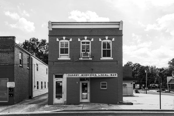 Black and white architectural photograph of the old brick building that houses Quarry Workers Local 829 in Ste Genevieve, Missouri.