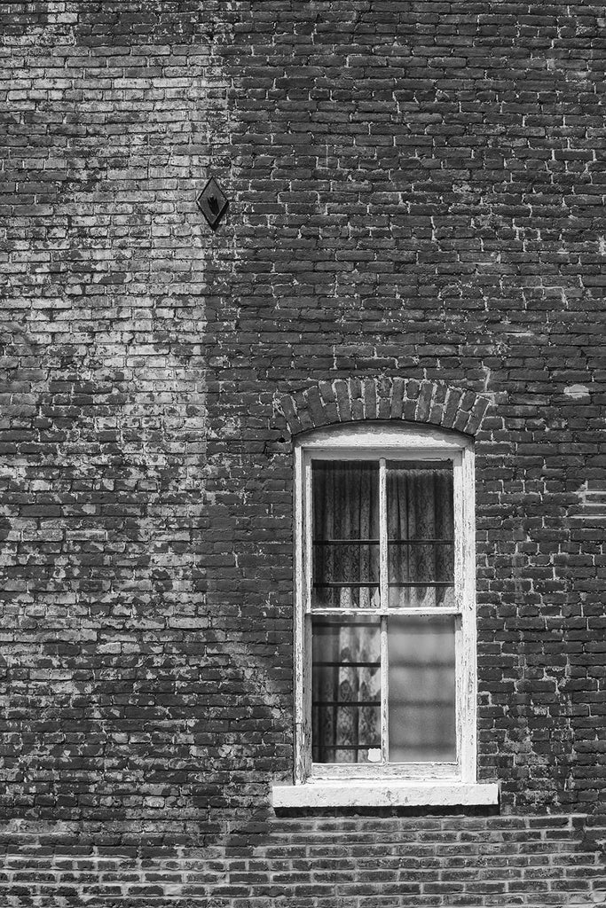 Black and white architectural detail photograph of lace curtains in the window of a historic brick building in picturesque Ste. Genevieve, Missouri.